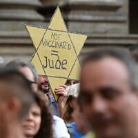 Illustrative -- A protester holds a Yellow Star reading 'Not Vaccinated = Jew' as protesters take part in a demonstration in Milan on July 24, 2021, against the introduction of a mandatory 'green pass' for indoor dining and entertainment area, in the aim to limit the spread of the Covid-19 (MIGUEL MEDINA / AFP)