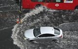 A car and a bus drives through deep water on a flooded road in The Nine Elms district of London on July 25, 2021. (JUSTIN TALLIS / AFP)