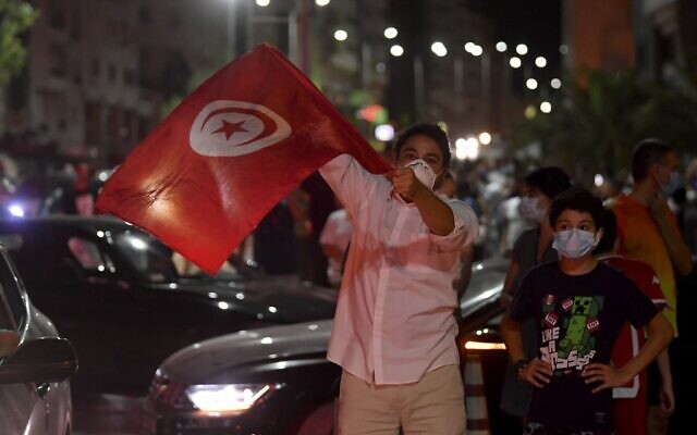 People celebrate in the street after Tunisian President Kais Saied announced the dissolution of parliament and Prime Minister Hichem Mechichi's government in Tunis on July 25, 2021, after a day of nationwide protest. (FETHI BELAID / AFP)