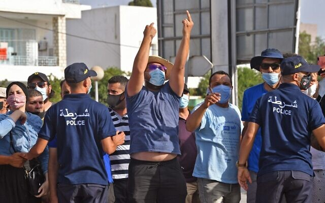 Tunisian policemen block protesters from advancing towards the Parliament building in the capital Tunis on July 26, 2021, following a move by the president to suspend the country's parliament and dismiss the prime minister (FETHI BELAID / AFP)