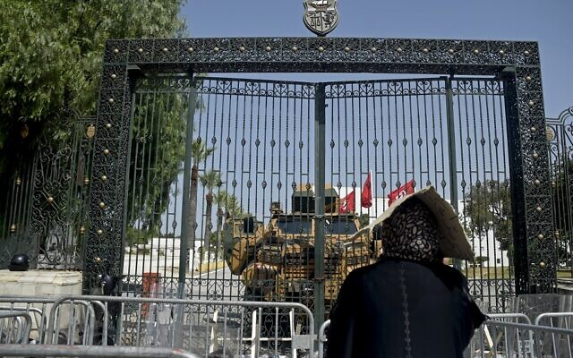 A Tunisian woman looks at the army-barricaded parliament building in the capital Tunis, on July 26, 2021, after the president dismissed the prime minister and ordered parliament closed for 30 days. (Yassine Mahjoub/AFP)