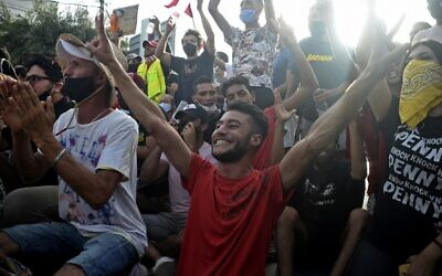 Supporters cheer outside the army-barricaded parliament building in the capital Tunis on July 26, 2021, after the president dismissed the prime minister and ordered parliament closed for 30 days (YASSINE MAHJOUB / AFP)