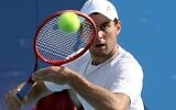 Russia's Aslan Karatsev returns the ball to France's Jeremy Chardy during their Tokyo 2020 Olympic Games men's singles second round tennis match at the Ariake Tennis Park in Tokyo on July 27, 2021. (Giuseppe CACACE / AFP)