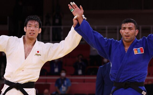 Gold medalist Japan's Takanori Nagase (white) and silver medalist Mongolia's Saeid Mollaei react after the judo men's -81kg gold medal bout during the Tokyo 2020 Olympic Games at the Nippon Budokan in Tokyo on July 27, 2021. (Jack GUEZ / AFP)