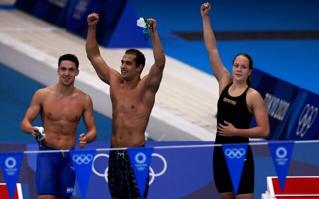 Israel's Anastasya Gorbenko (R), Itay Goldfaden (C) and Gal Cohen Groumi cheer after qualifying in a heat for the mixed 4x100m medley relay swimming event during the Tokyo 2020 Olympic Games at the Tokyo Aquatics Centre in Tokyo on July 29, 2021. (Photo by Odd ANDERSEN / AFP)