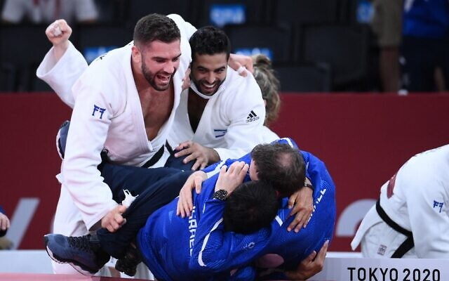 Team Israel celebrates winning the judo mixed team's bronze medal B bout against Russia during the Tokyo 2020 Olympic Games at the Nippon Budokan in Tokyo, on July 31, 2021. (Franck Fife/AFP)