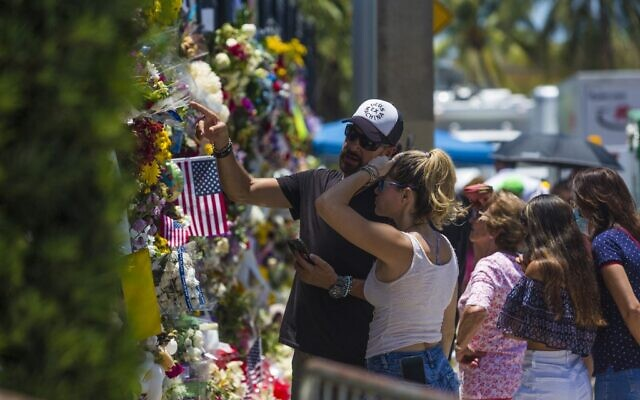 People observe the memorial to those missing outside the 12-story Champlain Towers South condo building that partially collapsed on July 4, 2021 in Surfside, Florida. (Saul MARTINEZ / Getty Images via AFP)