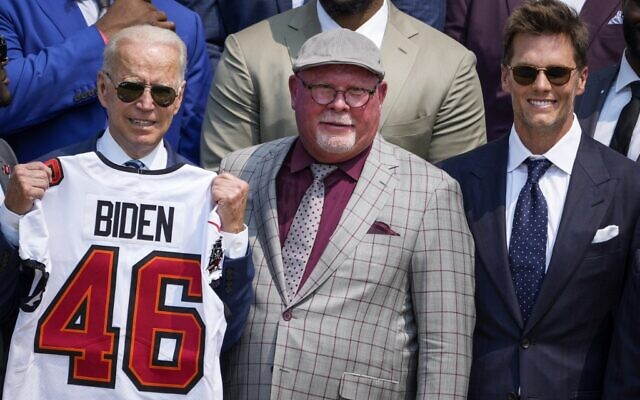 US President Joe Biden holds up a Buccaneers jersey while standing next to head coach Bruce Arians and quarterback Tom Brady, as he welcomes the 2021 NFL Super Bowl champions Tampa Bay Buccaneers during a ceremony on the South Lawn of the White House, on July 20, 2021, in Washington, DC. (Drew Angerer/Getty Images via AFP)