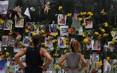 People look at a memorial that has pictures of some of the missing from the partially collapsed 12-story Champlain Towers South condo building on July 7, 2021 in Surfside, Florida. (Joe Raedle/Getty Images/AFP)