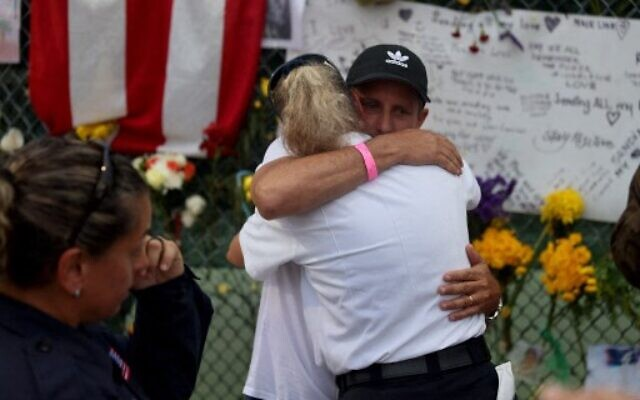 Pablo Langesfeld is hugged as he visits the memorial to the victims in the collapsed 12-story Champlain Towers South condo building as the search and rescue efforts are transitioning to a recovery operation on July 7, 2021 in Surfside, Florida. Mr. Langesfeld's daughter Nicole Langesfeld is one of the missing in the collapse of the building. (Joe Raedle/Getty Images/AFP)