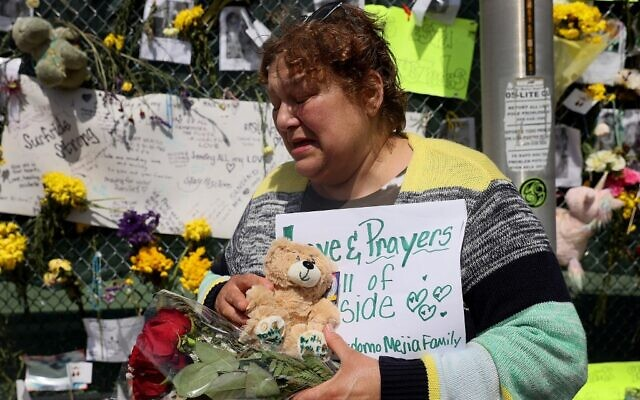 Maria Perdomo becomes emotional as she visits the memorial that includes pictures of some of the victims of the collapsed 12-story Champlain Towers South condo building on July 08, 2021 in Surfside, Florida. (Joe Raedle/Getty Images/AFP)