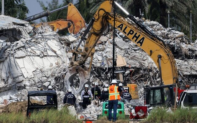 Rescue workers watch as excavators are used to dig through the rubble of the collapsed 12-story Champlain Towers South condo building on July 9, 2021 in Surfside, Florida. (Anna Moneymaker / Getty Images North America / Getty Images via AFP)