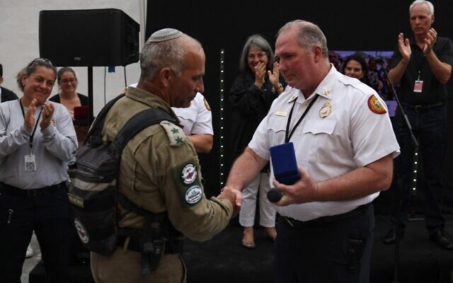 Miami Dade Fire Department Chief Alan Cominsky, left, presents a medal to Colonel Golan Vach, Commander of Israel Defense Forces National Rescue Unit during a send-off ceremony on July 10, 2021 in Surfside, Florida.  (Anna Moneymaker / GETTY IMAGES NORTH AMERICA / Getty Images via AFP)