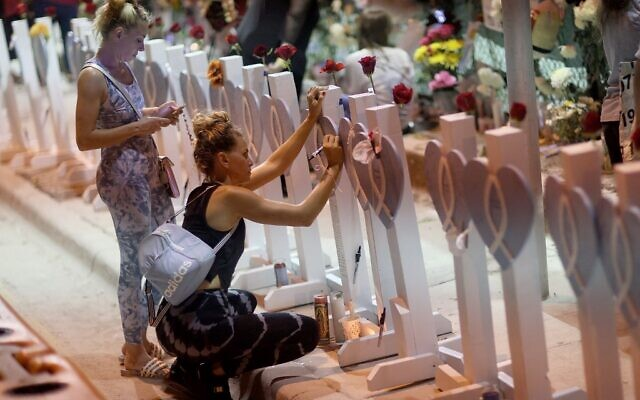People visit the memorial that has pictures of some of the victims from the partially collapsed 12-story Champlain Towers South condo building on July 15, 2021 in Surfside, Florida. (JOE RAEDLE / GETTY IMAGES NORTH AMERICA / Getty Images via AFP)