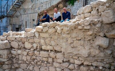 The excavation directors sitting on the exposed section of the First Temple-era protective wall on Jerusalem's eastern perimeter. (Yaniv Berman/ Israel Antiquities Authority)