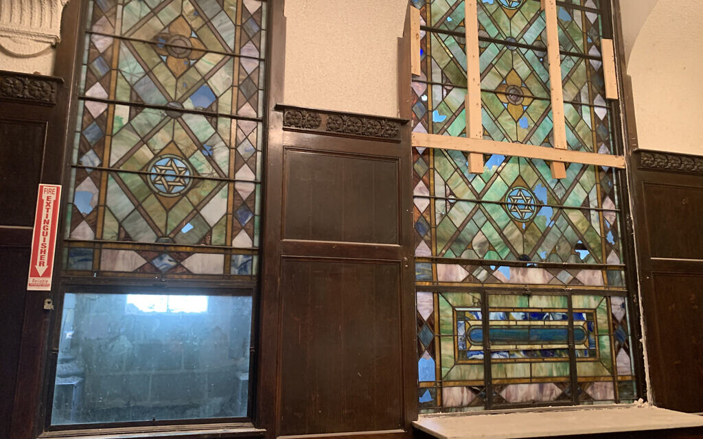 Stained-glass windows featuring Jewish iconography have survived decades longer than the congregation itself in Chicago's decrepit B'nei Bezalel building. Tom and Amber Ginsburg, who are renovating the structure, are inspired by the building's legacy as 'a holy place.' (Naomi Waxman/JTA)