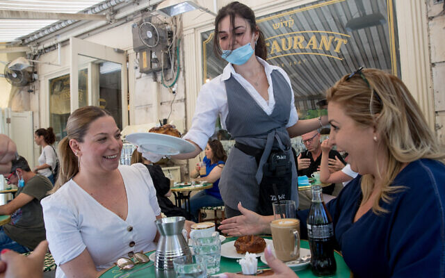 Customers sitting at Cafe Kadosh in Jerusalem, May 2020. The restaurant is one of hundreds in Israel that has opted for kosher certification outside the auspices of Israel's Chief Rabbinate. (Yonatan Sindel/Flash90)