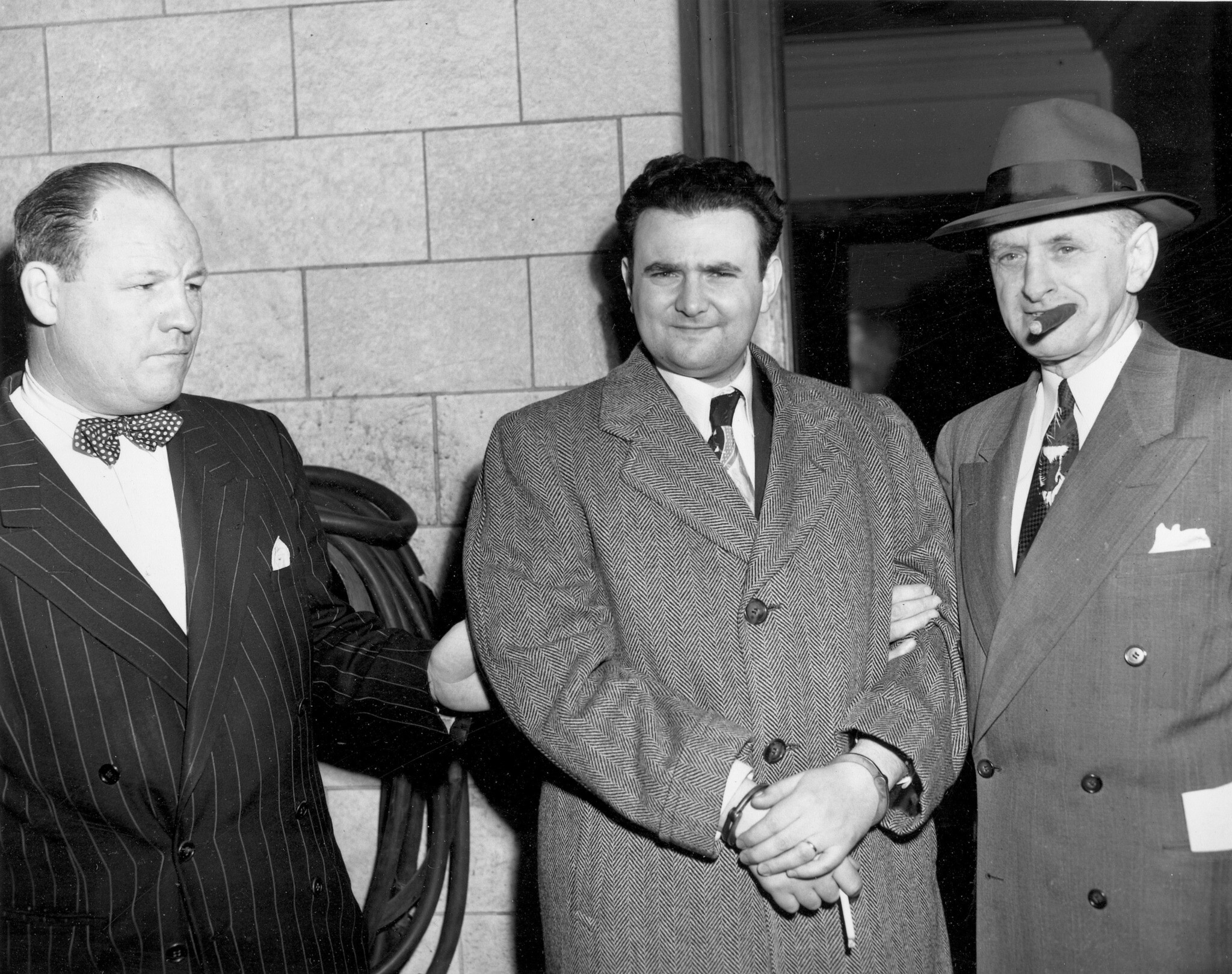 A handcuffed David Greenglass is escorted by US Deputy Marshall Eugene Fitzgerald from Federal Courthouse in New York City after being sentenced to 15 years in prison for conspiracy to spy for the Soviet Union, April 6, 1951. (AP Photo)