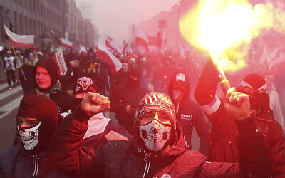 In this Friday, Nov. 11, 2016 file photo, nationalists, burning flares as they march in large numbers through the streets of Warsaw to mark Poland's Independence Day in Warsaw, Poland.  (AP Photo/Czarek Sokolowski, File)