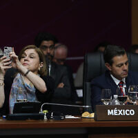 Mexico's then-president Enrique Pena Nieto takes notes as an unidentified Mexican diplomat takes pictures with her mobile phone during the plenary session at the Americas Summit in Lima, Peru, Saturday, April 14, 2018. (AP/Karel Navarro)