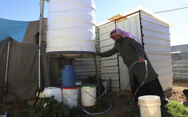 Illustrative: A Syrian man fills a bucket with water inside Zaatari, the largest camp for Syrian refugees in Mafraq, Jordan, on Sunday, Feb. 3, 2019.  (AP/Raad Adayleh)