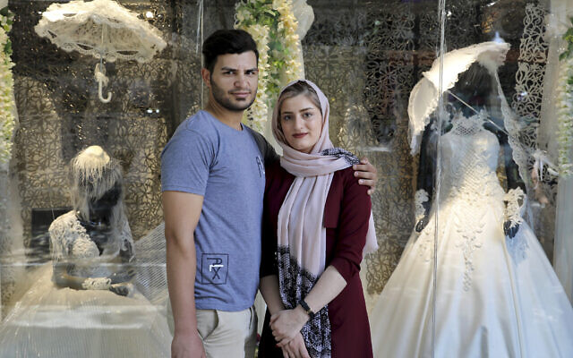 Illustrative: Newly married Iranian couple Mohammad Davoodi, 28, and his wife Mahsa Asadzadeh, 20, pose for a photo in front of a wedding dress shop in downtown Tehran, Iran, on July 3, 2019. (AP/Ebrahim Noroozi)
