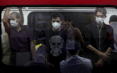 Illustrative: People wearing protective face masks to help prevent the spread of the coronavirus stand inside a train in Tehran, Iran on July 8, 2020. (AP/Ebrahim Noroozi)