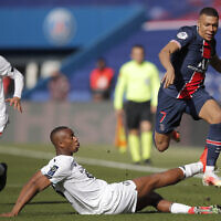 PSG's Kylian Mbappe, right, fights for the ball with Lille's Tiago Djalo during the French League One soccer match between Paris Saint Germain and Lille, at the Parc des Princes stadium, in Paris, France, on April 3, 2021. (AP Photo/Christophe Ena)