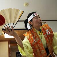 Olympic fan Kyoko Ishikawa shows her cheering at her home, April 10, 2021, in Tokyo. (AP/Eugene Hoshiko)
