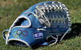 The glove of Israel Olympic baseball player Jake Roseberg sits on the field at Salt River Fields spring training facility, Wednesday, May 12, 2021, in Scottsdale, Arizona. Israel has qualified for the six-team baseball tournament at the Tokyo Olympic games which will be its first appearance at the Olympics in any team sport since 1976. (AP Photo/Matt York)