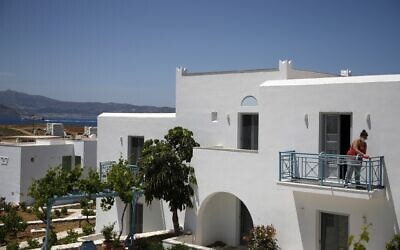 A worker cleans the balcony of a hotel room in Agios Prokopios village, on the Aegean island of Naxos, Greece, May 12, 2021 (AP Photo/Thanassis Stavrakis)