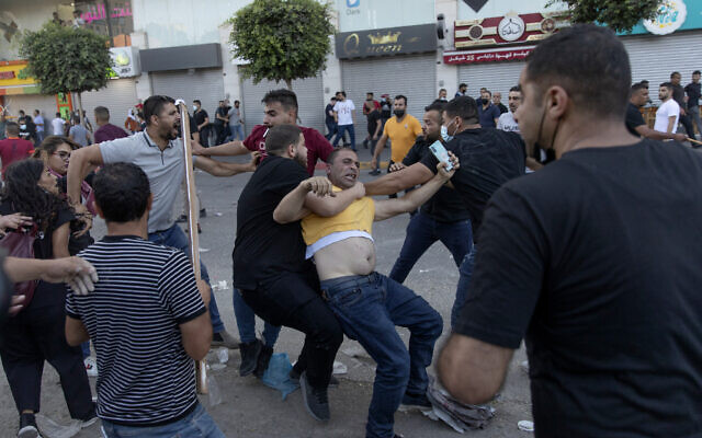 Palestinian security officers in plainclothes detain a demonstrator during clashes that erupted following a rally protesting the death of Palestinian Authority outspoken critic Nizar Banat, in the West Bank city of Ramallah, on June 26, 2021. (AP Photo/Nasser Nasser)