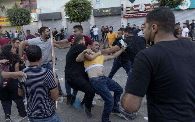 Palestinian security officers in plainclothes detain a demonstrator during clashes that erupted following a rally protesting the death of outspoken PA critic Nizar Banat, in the West Bank city of Ramallah, on Saturday, June 26, 2021. (AP Photo/Nasser Nasser)