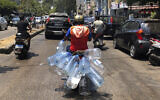 A man rides his scooter with empty water bottles to fill them with gasoline, in Beirut, Lebanon, June 23, 2021. (AP/Hussein Malla)