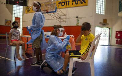 Medical personnel test Israeli children the coronavirus at a basketball court turned into a coronavirus testing center, in Binyamina, Israel, Tuesday, June 29, 2021. (AP Photo/Ariel Schalit)
