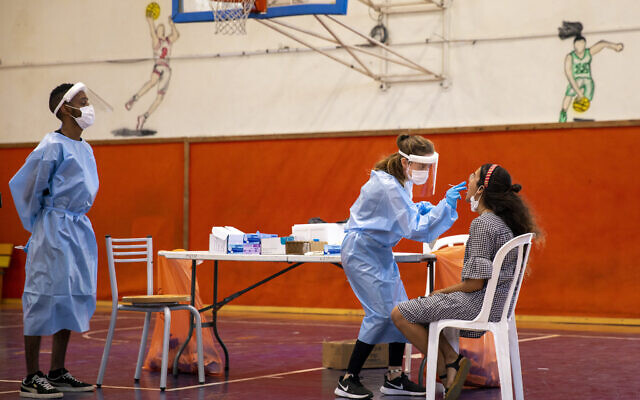A medical worker tests for the coronavirus at a basketball court turned into a coronavirus testing center in Binyamina, June 29, 2021. (AP Photo/Ariel Schalit)