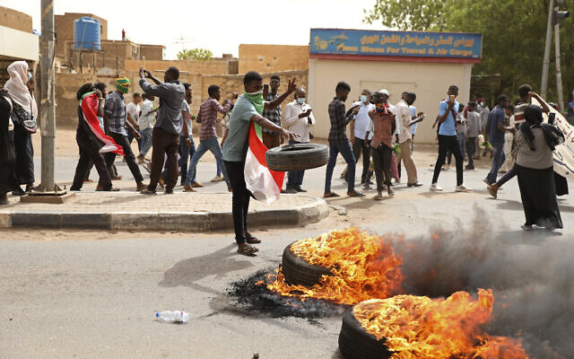 A demonstrator throws a tire on a fire during a protest over economic conditions, in Khartoum, Sudan, Wednesday, June 30, 2021. (AP Photo/Marwan Ali)