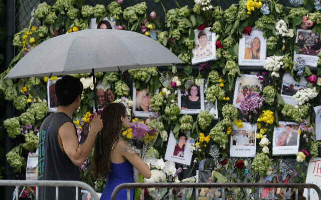 Visitors bring flowers to add to a makeshift memorial for the scores of people who were left missing after the Champlain Towers South condo building partially collapsed nearly a week ago, Wednesday, June 30, 2021, in Surfside, Fla.. (AP Photo/Gerald Herbert)