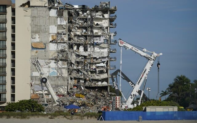 Workers peer up at the rubble pile at the partially collapsed Champlain Towers South condo building, on Thursday, July 1, 2021, in Surfside, Florida (AP Photo/Mark Humphrey)