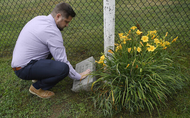 Brett Eagleson, son of September 11 victim Bruce Eagleson, wipes grass off a memorial stone for his father at the baseball field where his father use to coach on July 2, 2021, in Middletown, Connecticut (AP Photo/ Jessica Hill)