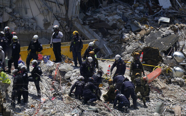 Search and rescue personnel work atop the rubble at the Champlain Towers South condo building, where scores of victims remain missing more than a week after it partially collapsed, on July 2, 2021, in Surfside, Florida. (AP Photo/Mark Humphrey)