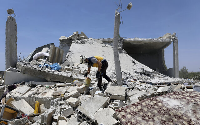 A civil defense worker inspects a destroyed building after shelling hit the town of Ibleen, a village in southern Idlib province, Syria, July 3, 2021. (AP Photo/Ghaith Alsayed)