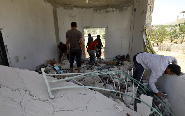 People inspect a damage house after shelling hit the town of Ibleen, a village in southern Idlib province, Syria, July 3, 2021. (AP Photo/Ghaith Alsayed)