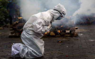 In this July 2, 2021, file photo, a woman breaks down as she prays before the cremation of a relative who died of COVID-19 in Gauhati, India. The global death toll from COVID-19 has eclipsed 4 million as the crisis increasingly becomes a race between the vaccine and the highly contagious delta variant. (AP Photo/Anupam Nath, File)