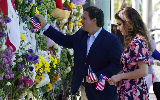 Florida Gov. Ron DeSantis, left, and his wife Casey leave flags at a makeshift memorial near the Champlain Towers South condo building, where scores of victims remain missing more than a week after it partially collapsed, Saturday, July 3, 2021, in Surfside, Fla. (AP Photo/Lynne Sladky)