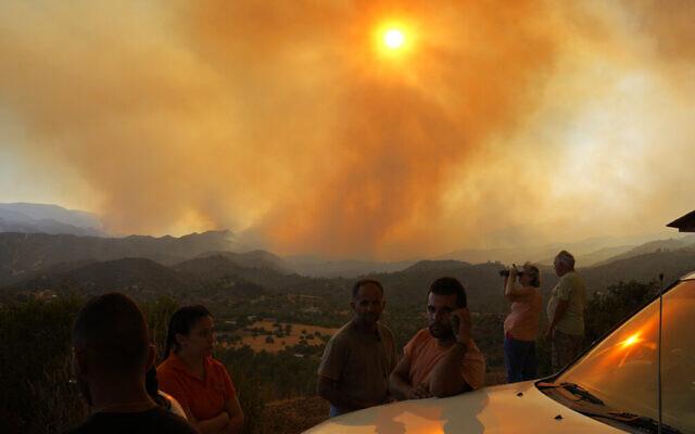 Residents of villages watch a fire in the Larnaca mountain region on July 3, 2021. (AP Photo/Petros Karadjias)
