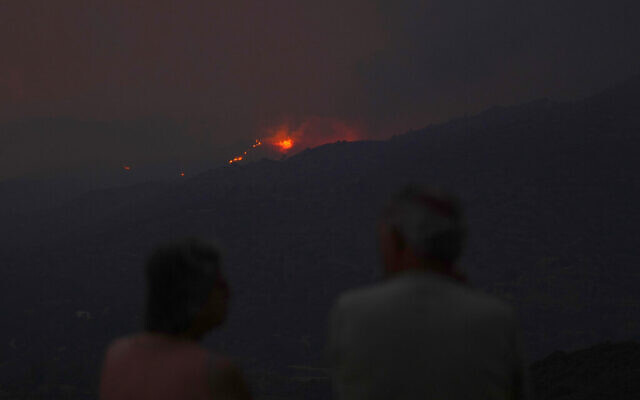 Residents of a village watch a fire in the Larnaca mountain region, Cyprus, July 3, 2021. (AP Photo/Petros Karadjias)