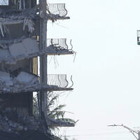 Workers stand watch from a lift beside the partially collapsed Champlain Towers South condo building, where demolition experts were preparing to bring down the precarious still-standing portion, Sunday, on July 4, 2021, in Surfside, Florida. (AP/Lynne Sladky)