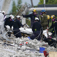 In this Monday, July 5, 2021, file photo, rescue workers move a stretcher containing recovered remains at the site of the collapsed Champlain Towers South condo building, in Surfside, Florida. (AP/Lynne Sladky)