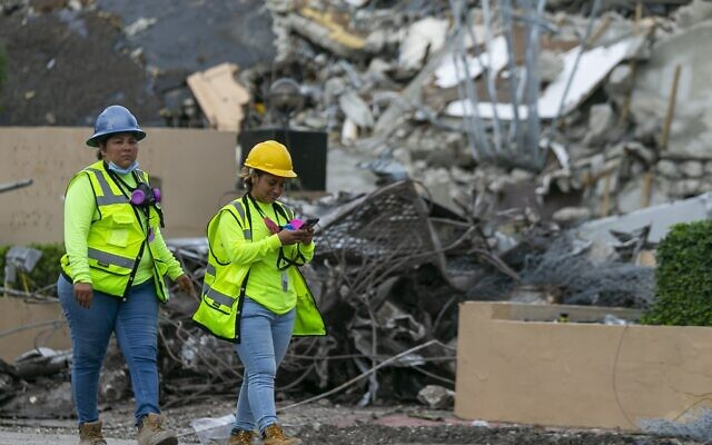 A workers make her way past the rubble and debris of the Champlain Towers South condo in Surfside, Florida on July 6, 2021. (Matias J. Ocner/Miami Herald via AP)